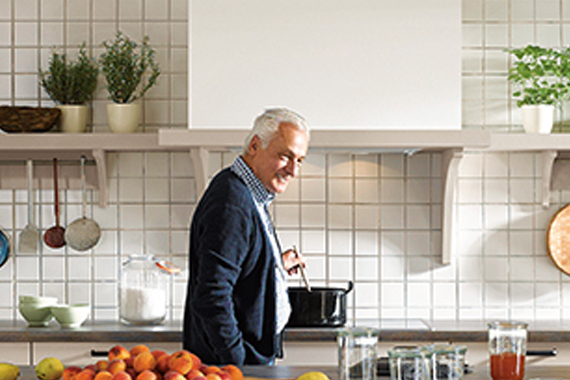 Een oudere man die graag en veel kookt in een landelijke keuken van Boncquet