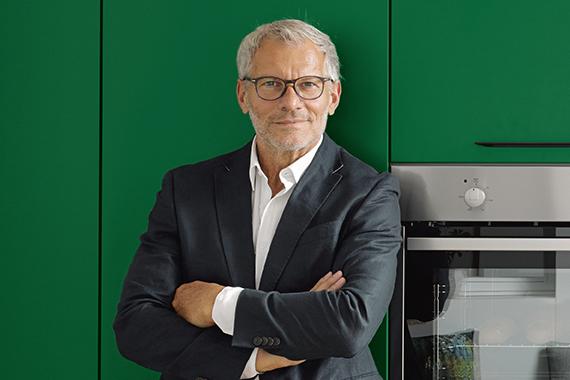 homme dans une nouvelle cuisine équipée verte Boncquet réfléchissant le prix